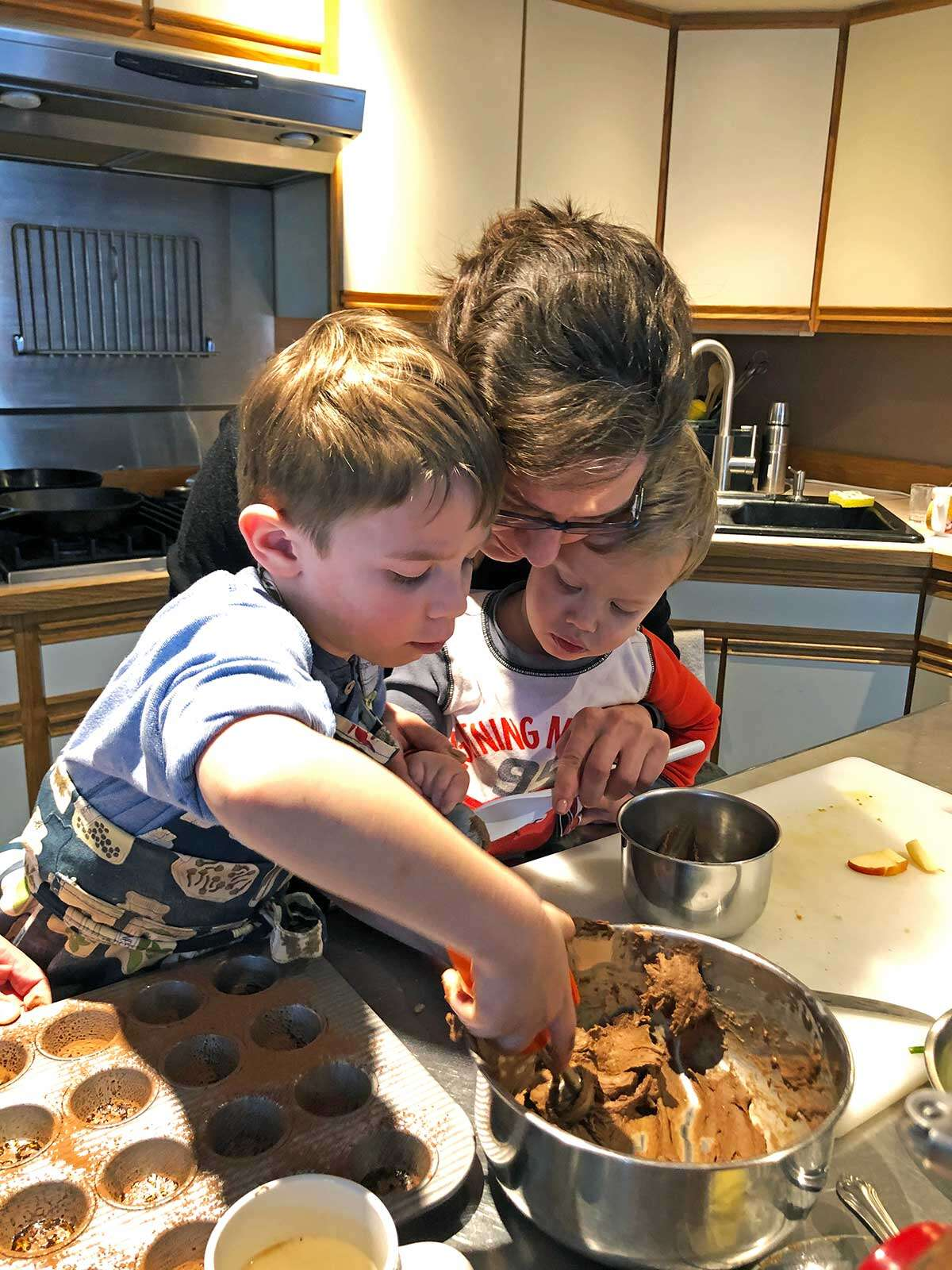 A mother and her two children scooping batter out of a bowl into a mini muffin pan.