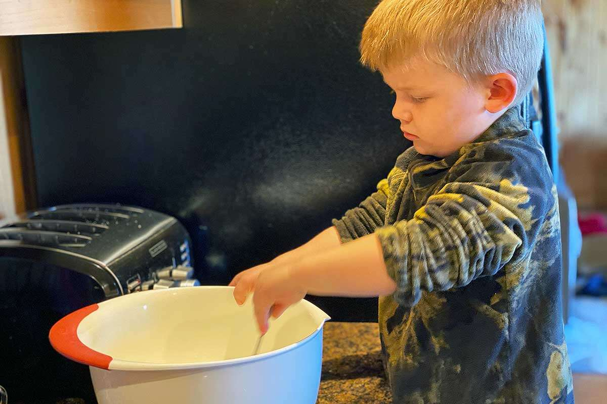 A young baker mixing a bowl of banana bread bread
