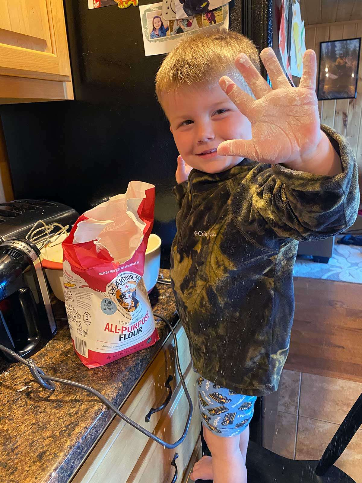 A child with a bag of King Arthur Flour in the kitchen holding out a flour-covered hand