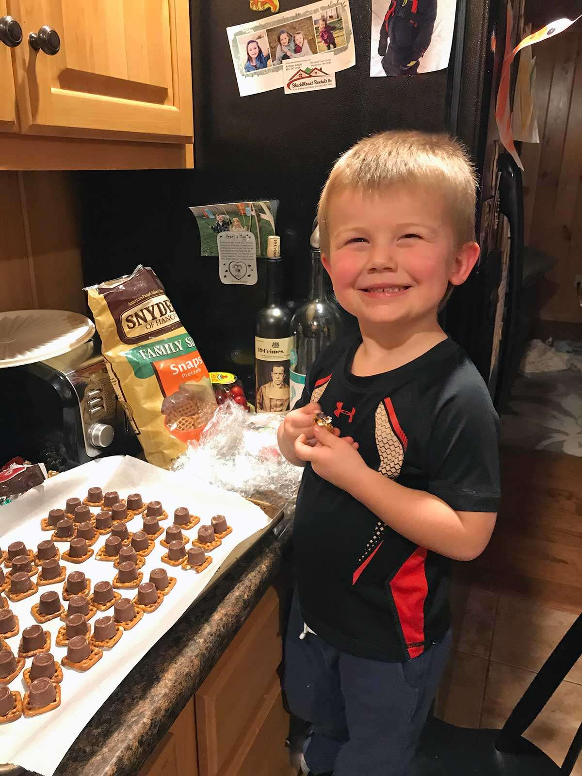 A small child making no-bake energy bites at home, smiling