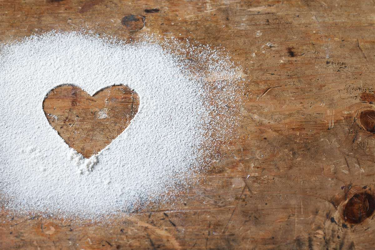 A heart drawn in a dusting of flour on a wooden table