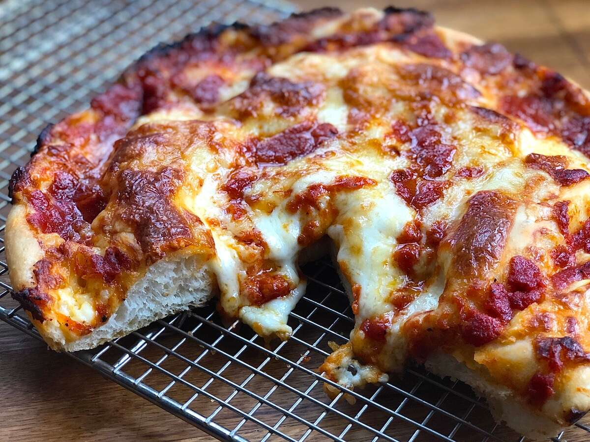 Crispy Cheesy Pan Pizza topped with mozzarella, provolone, and cheddar cheeses.