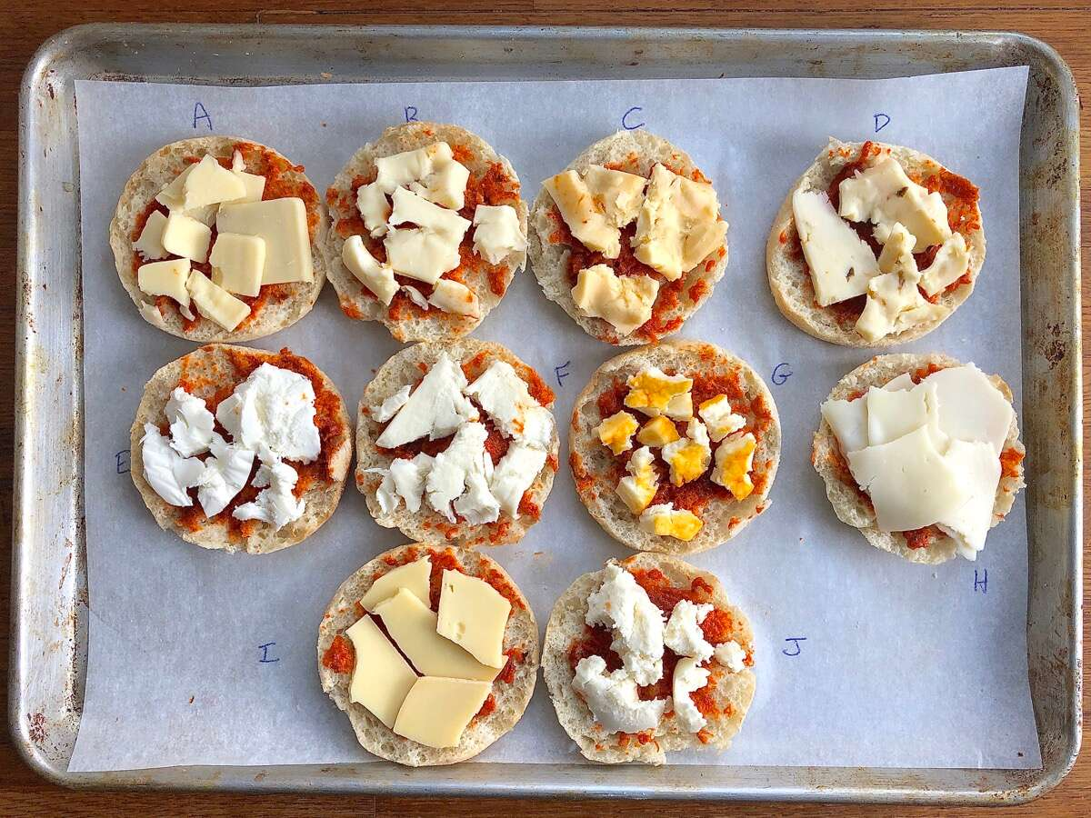10 English muffin halves topped with tomato sauce, each one with a different type of cheese, ready to bake.