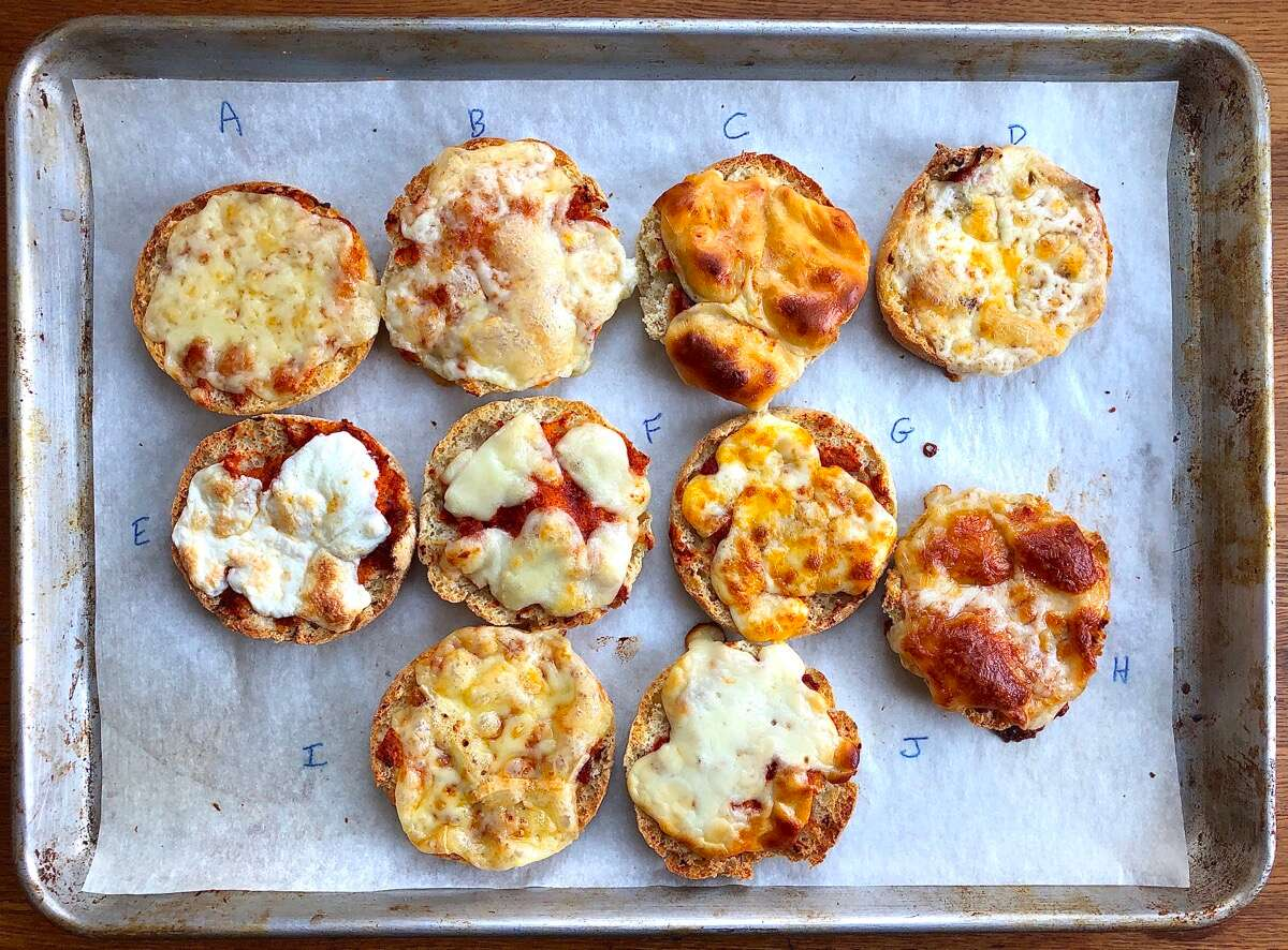 10 English muffin halves topped with sauce and different cheeses, baked until cheeses have melted.