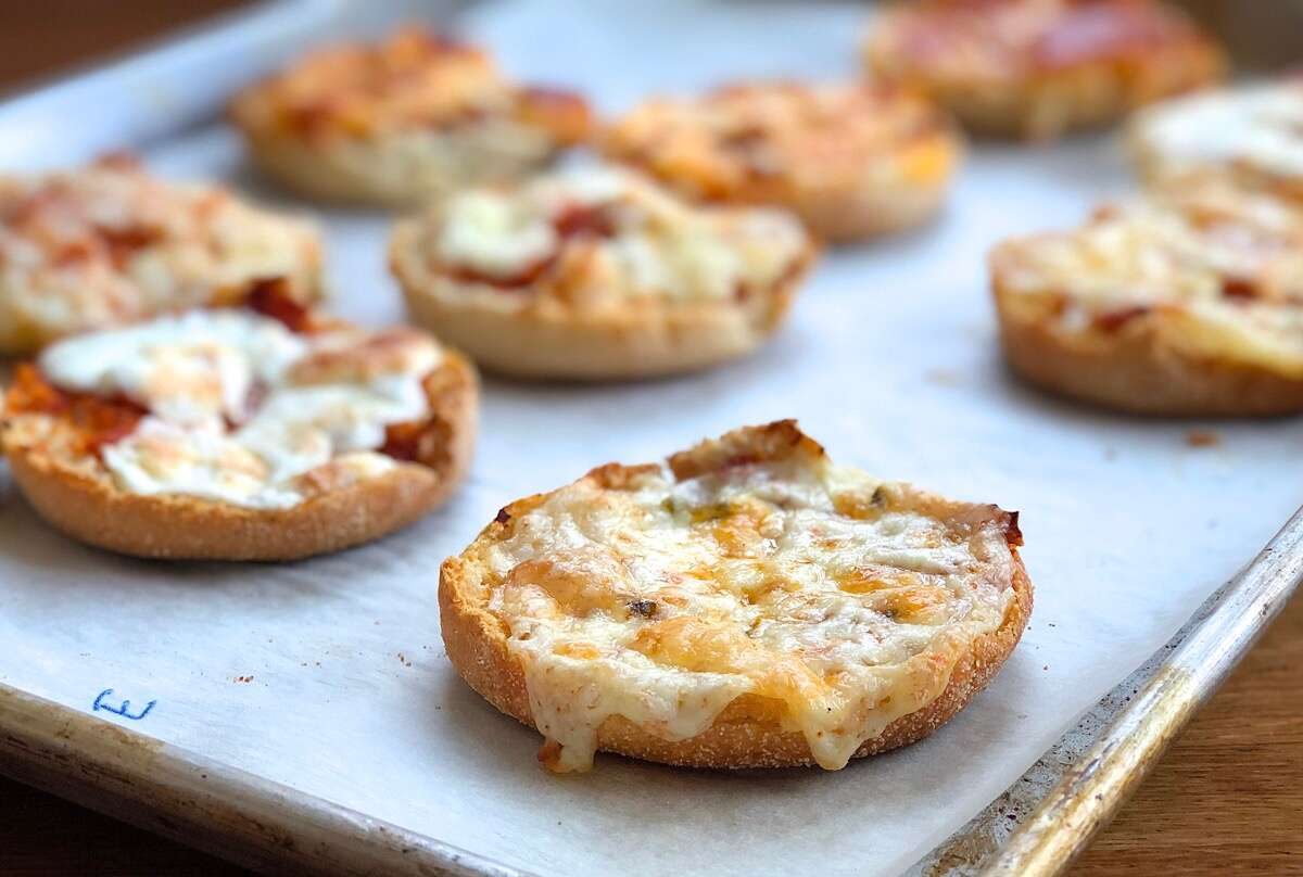 English muffin topped with sauce and cheddar cheese, baked.