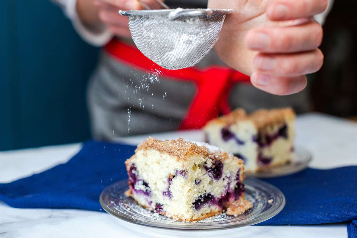 A baker dusting a slice of Blueberry Buckle Coffeecake with confectioners' sugar