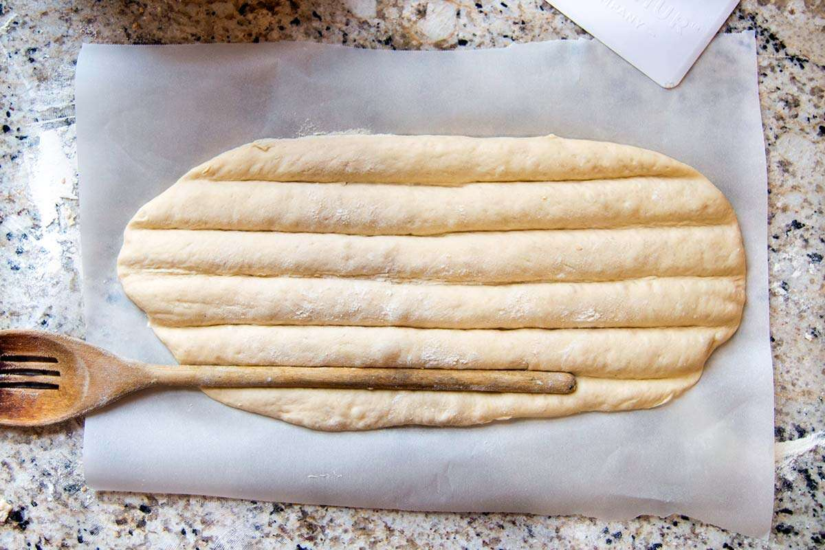 Shaped bread dough with wooden spoon making grooves