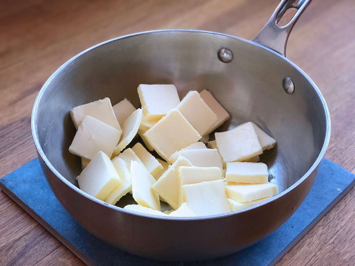 Pats of butter in a light-colored skillet, ready to melt and simmer into brown butter.