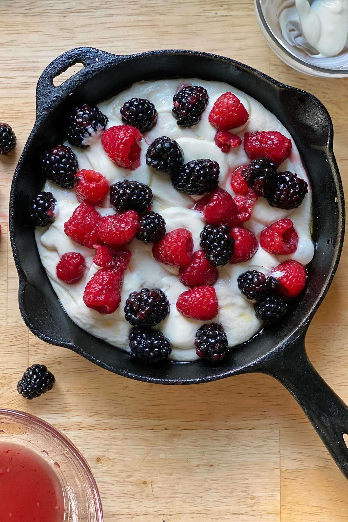 Pizza dough in a cast iron pan topped with sweetened mascarpone and fresh berries