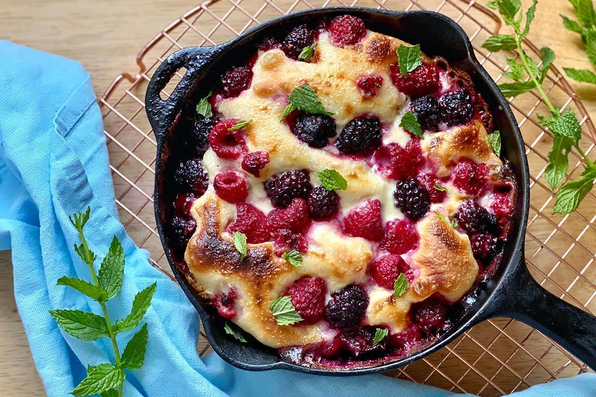 A brunch pizza topped with sweetened mascarpone, fresh berries, and torn mint leaves