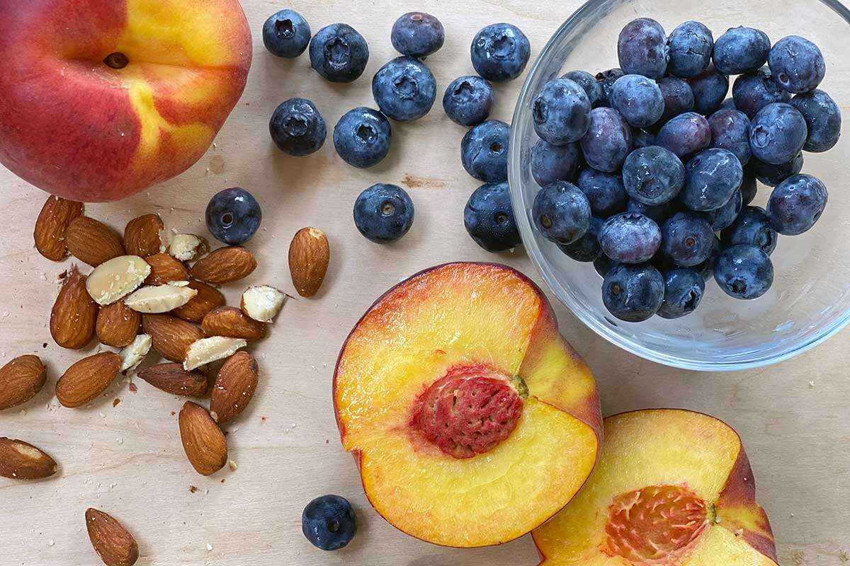 Peaches, blueberries, and almonds on a kitchen table