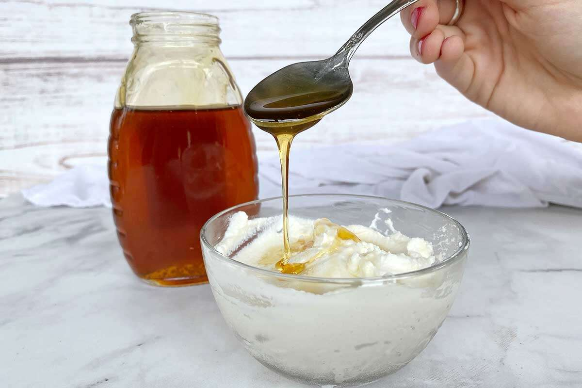 A small bowl of ricotta being drizzled with honey