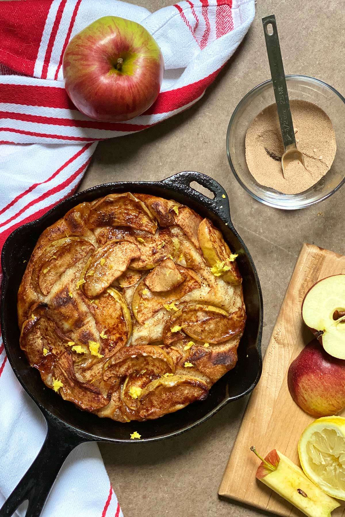 A cast iron pizza topped with sliced apples, cinnamon-sugar, and brown butter