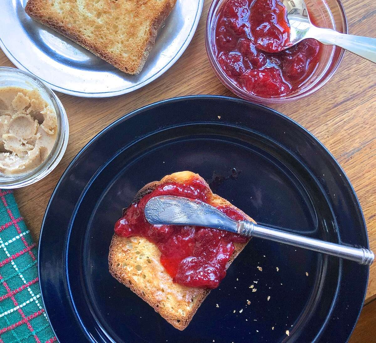 Toast on a plate, spread with butter and strawberry jam.