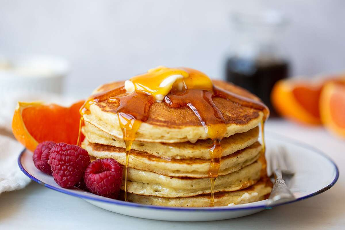 A stack of pancakes topped with butter, fruit, and maple syrup