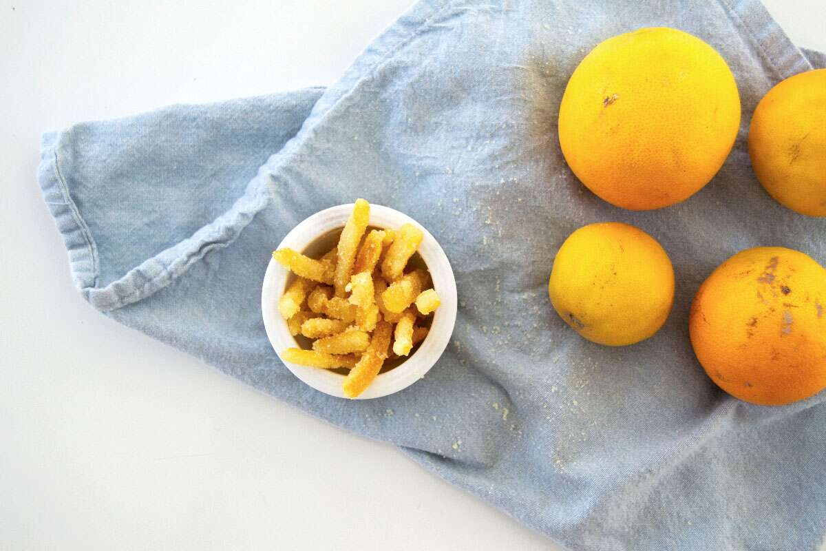 Small bowl of candied citrus peels next to three oranges