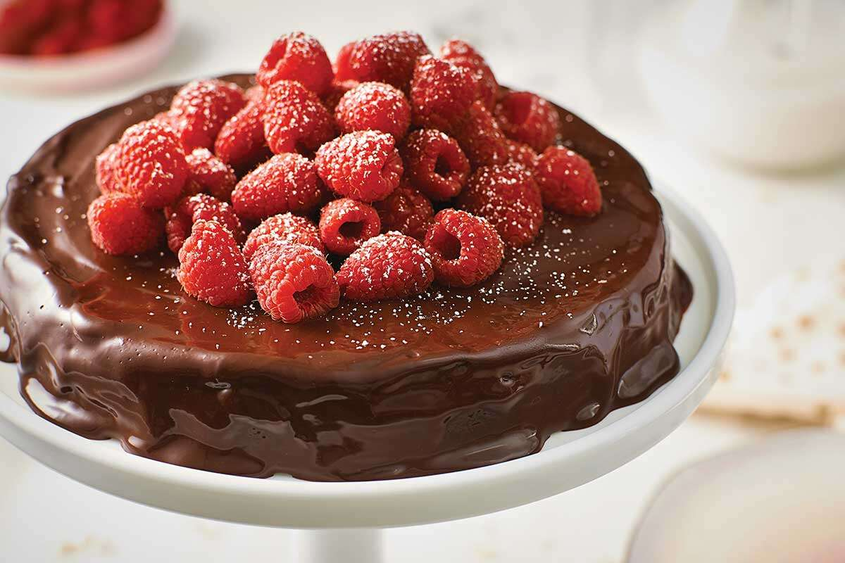 A flourless chocolate cake topped with raspberries