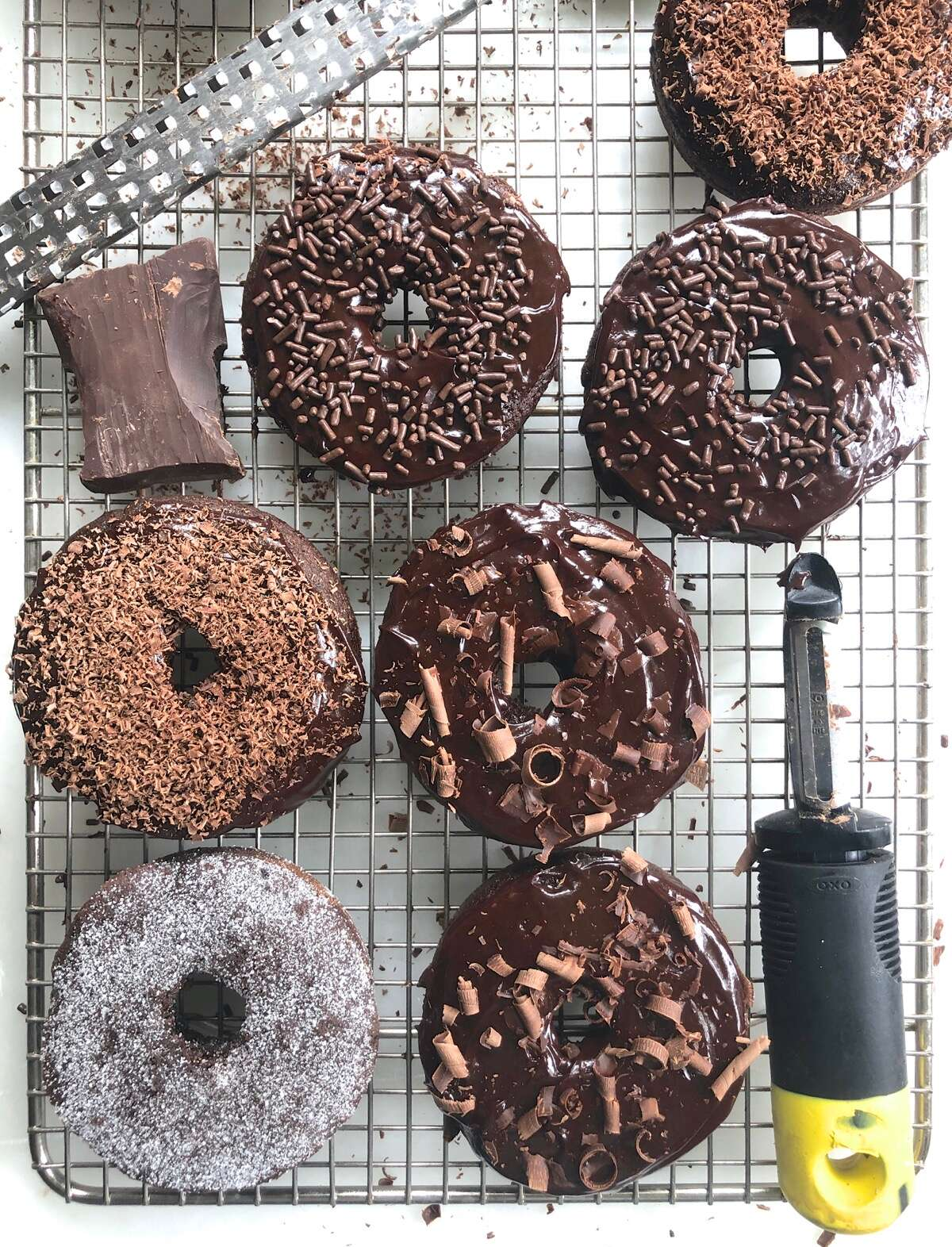 Frosted and sprinkled Chocolate Fudge Cake Doughnuts on a cooling rack.