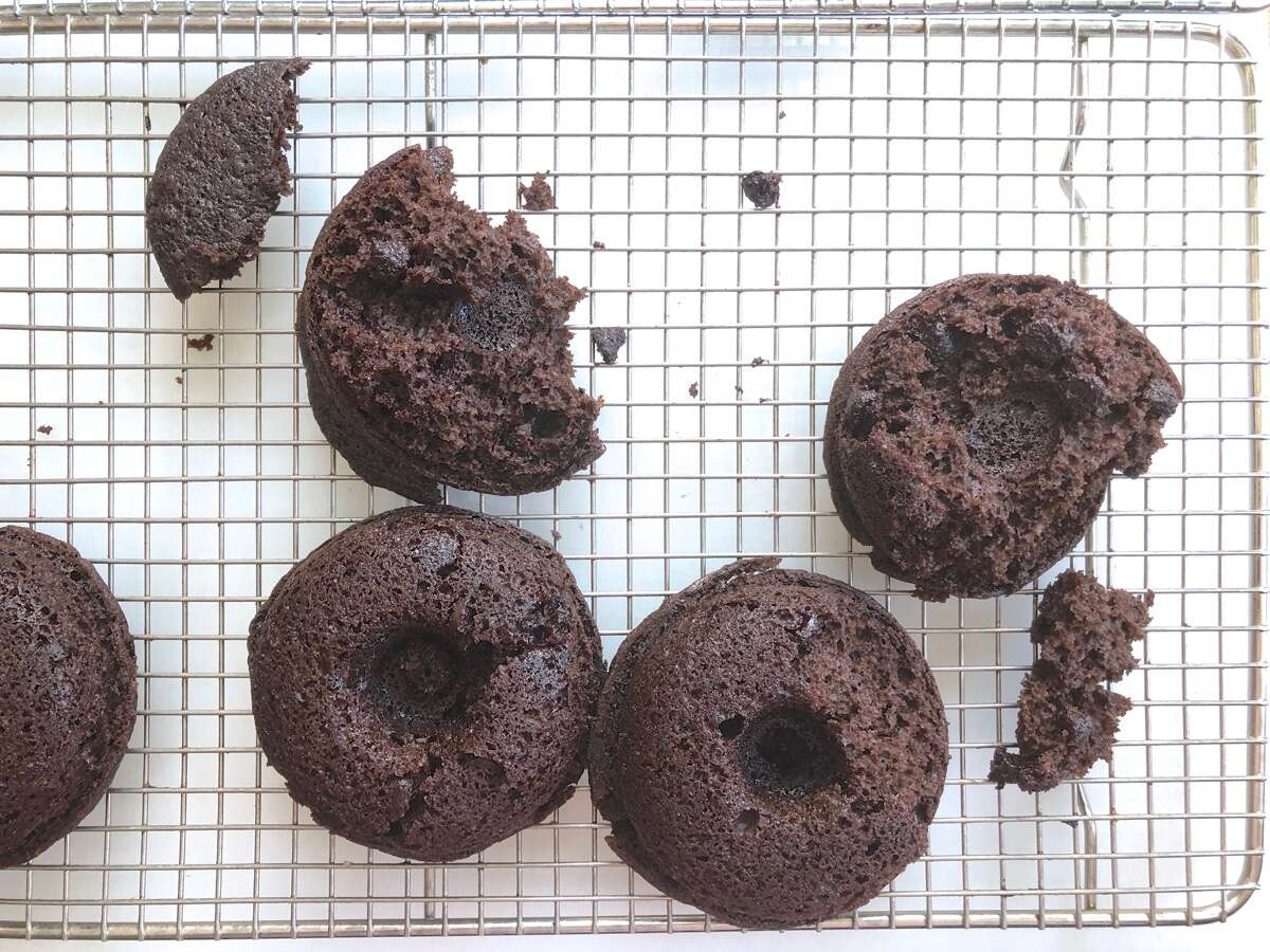 Crumbled chocolate doughnuts on a cooling rack.