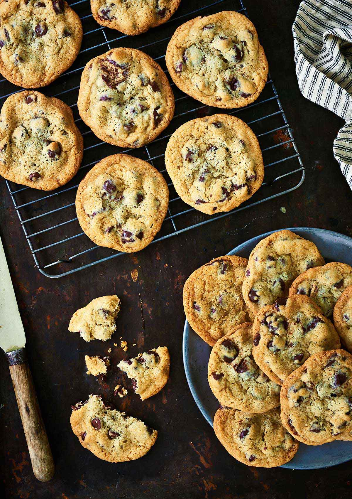 Freshly baked chocolate chip cookies on a cooling rack and on a plate