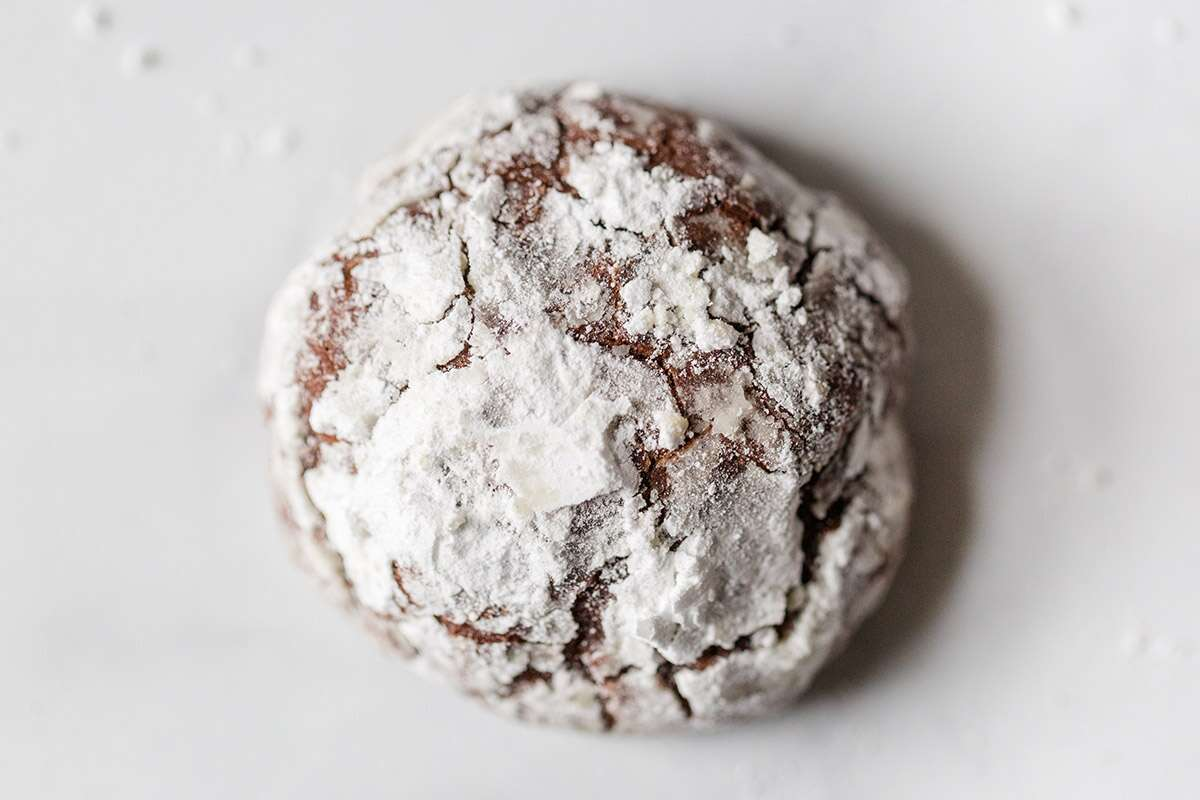 A close-up shot of a Chocolate Crinkle on a marble surface showing the cracks in the sugar coating