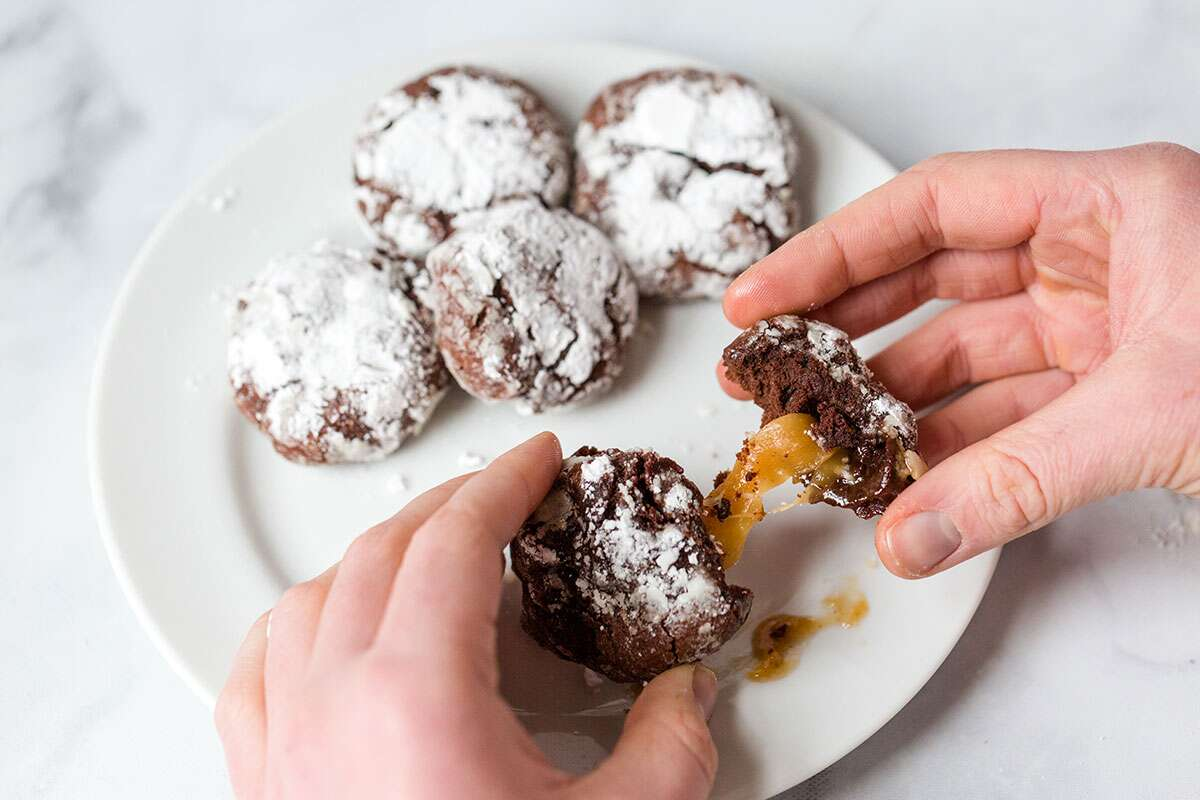 A baker breaking open a Chocolate Crinkle to reveal caramel inside