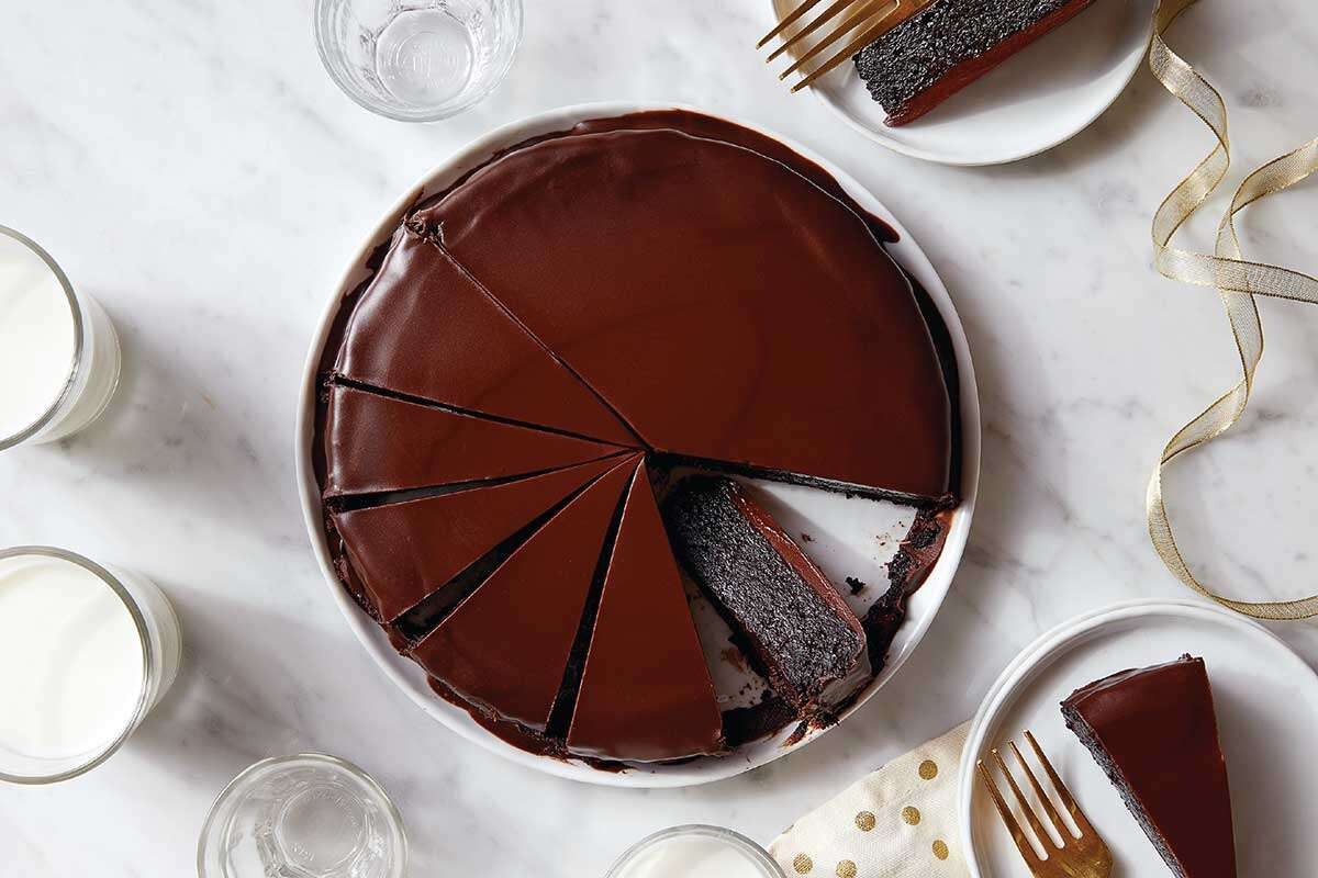 A flourless chocolate cake topped with ganache on a serving plate, cut into slices