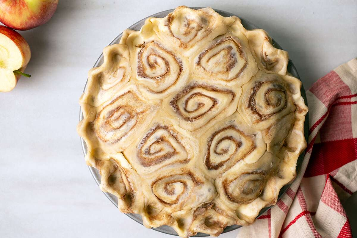 An unbaked apple pie with a cinnamon bun pie crust
