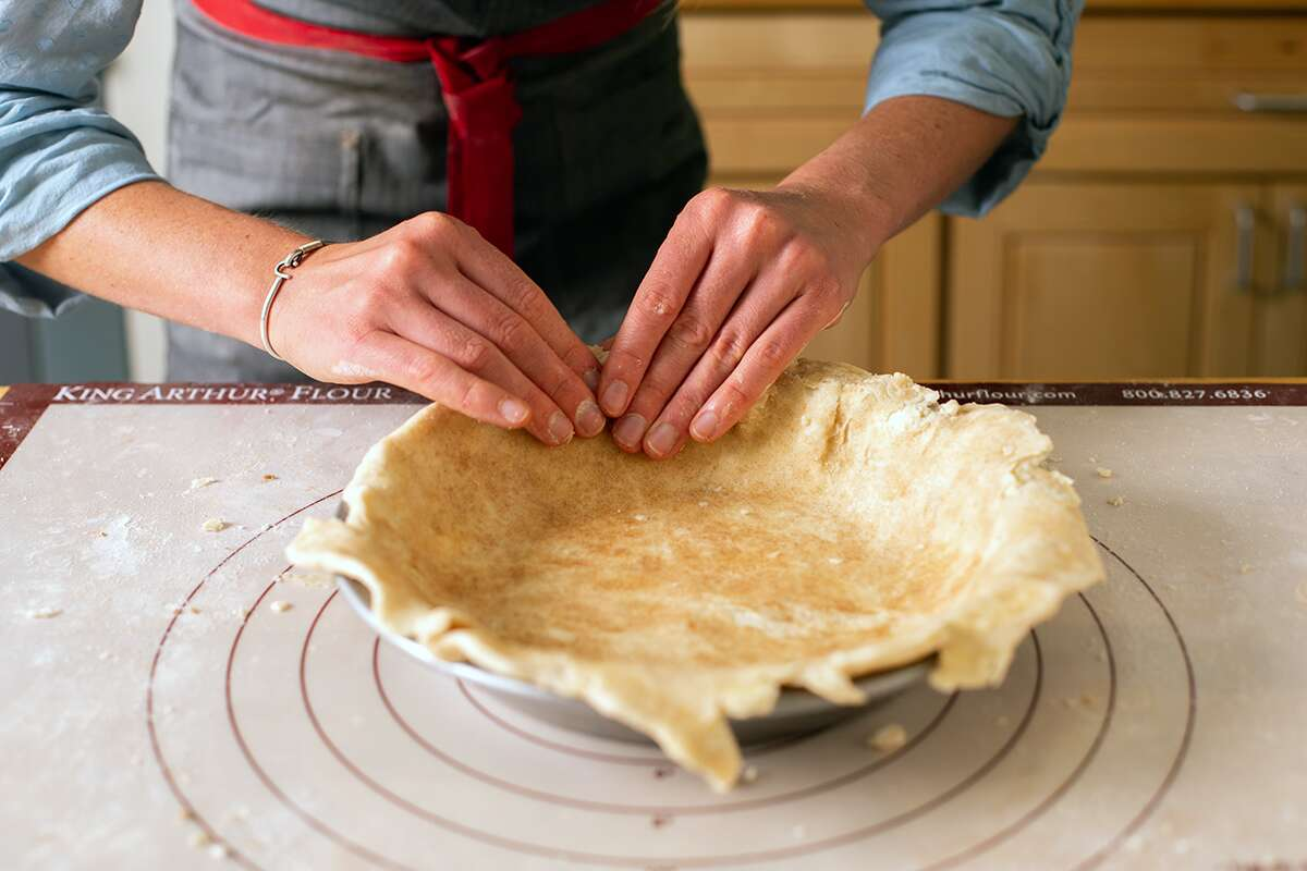 A baker shaping the bottom crust for a cinnamon bun apple pie into a pan