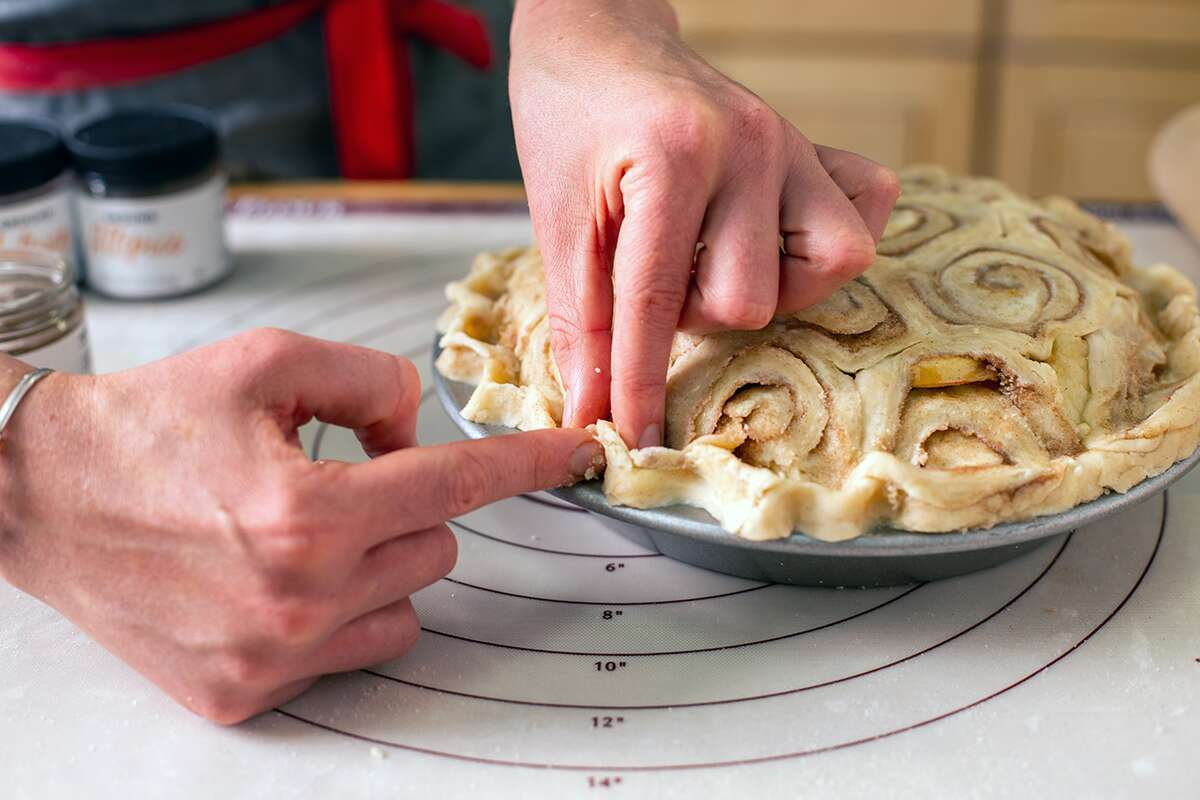A baker arranging a cinnamon bun crust on top of an apple pie