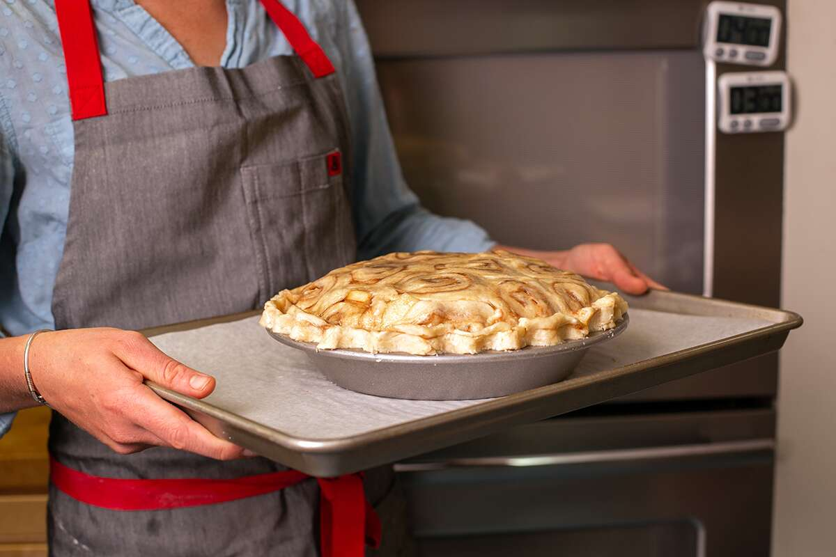 A baker holding an unbaked cinnamon bun apple pie, ready to go in the oven