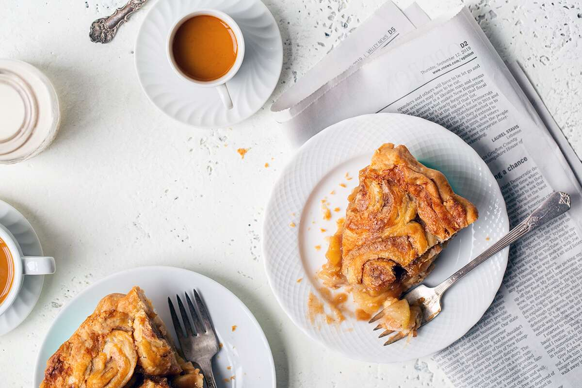 Slices of cinnamon bun apple pie on plates with espresso