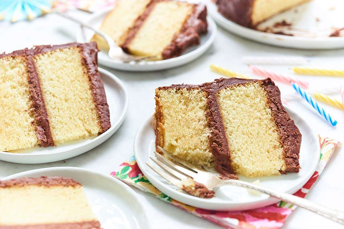Slices of yellow cake with chocolate frosting on small plates