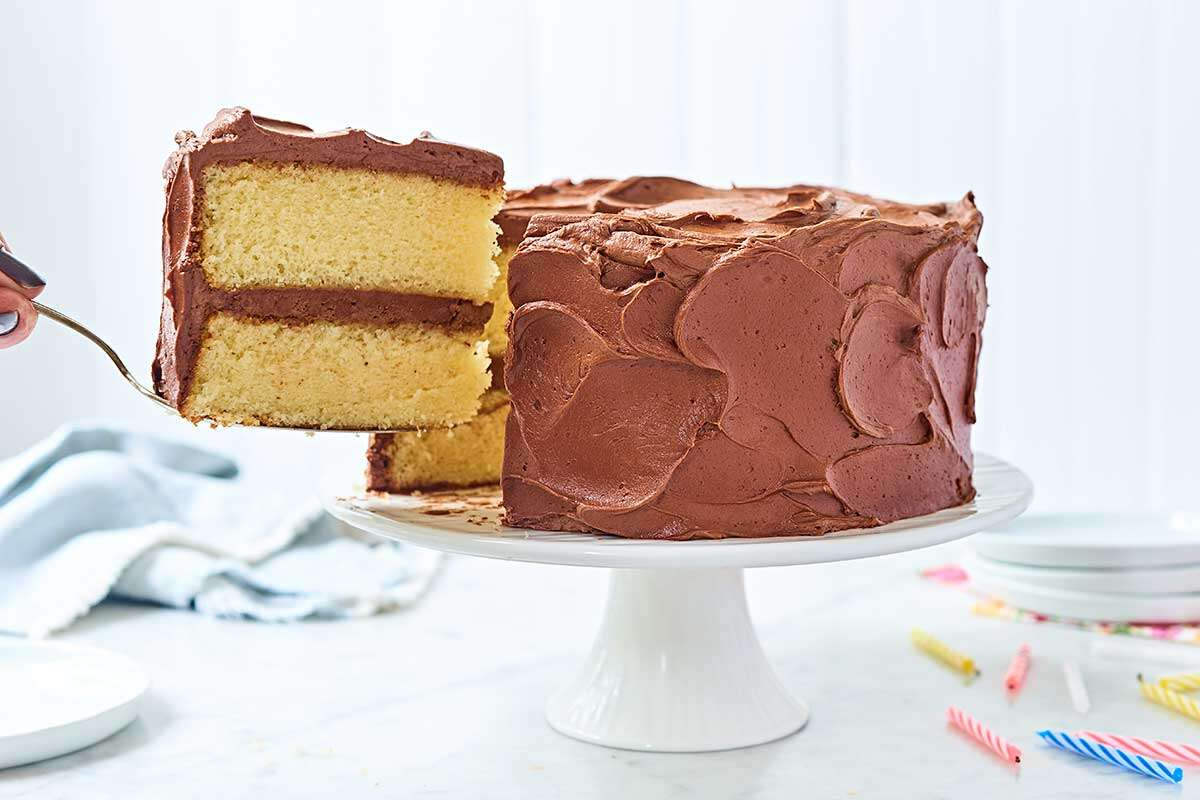 A slice being remove from a Classic Birthday Cake: yellow layer cake coated in chocolate fudge frosting