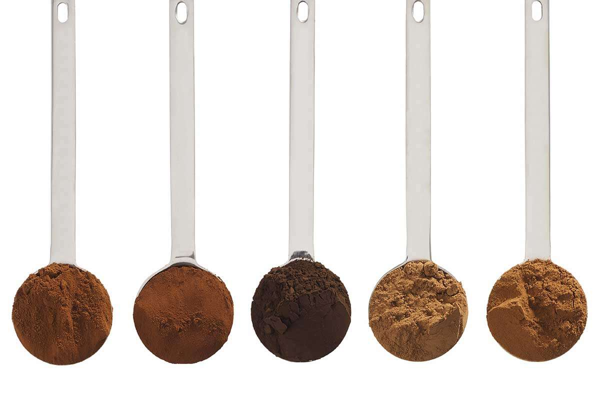 Five tablespoons full of cocoa powder lined up, each a different shade of brown