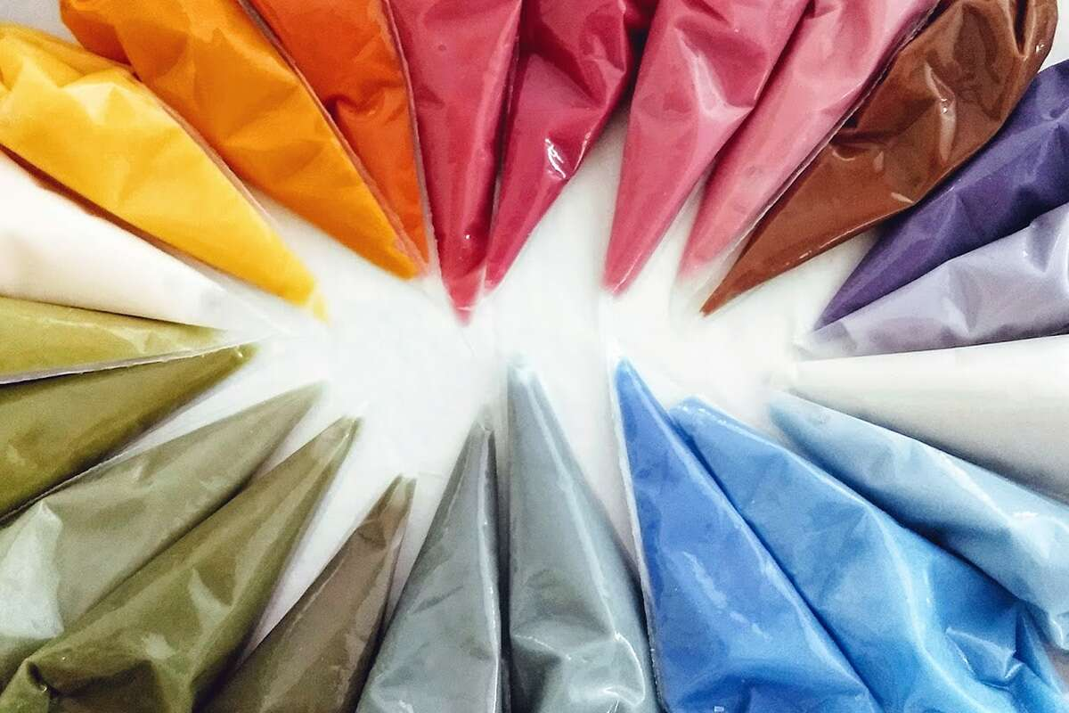 An array of pastry bags filled with naturally-colored icing, all colors of the rainbow