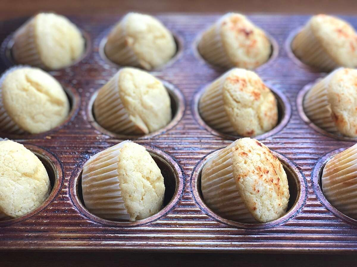 Baked corn muffins tilted in the wells of a muffin pan cooling off