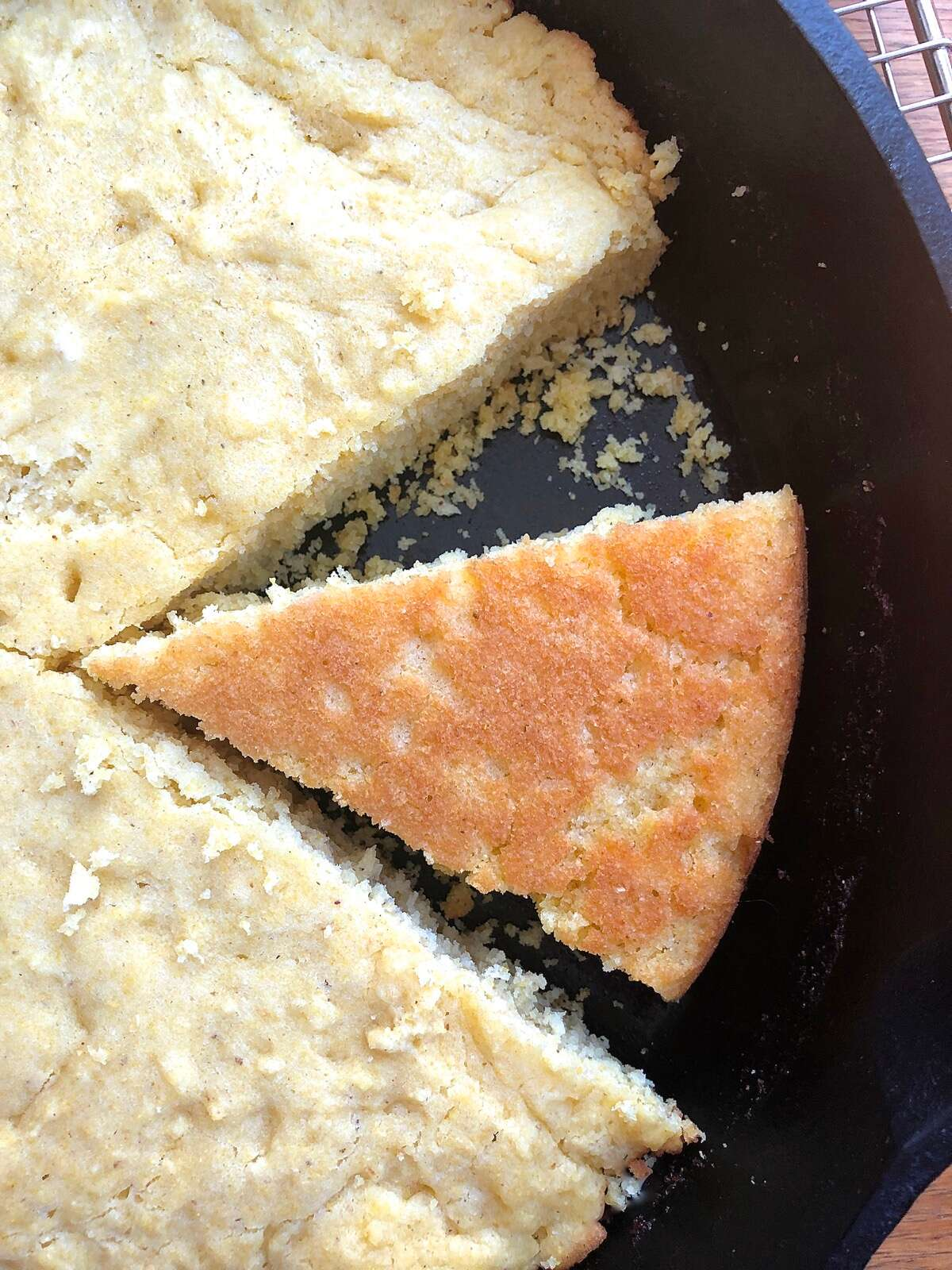 A wedge of baked cornbread turned over in a cast-iron skillet to show its golden brown crust.