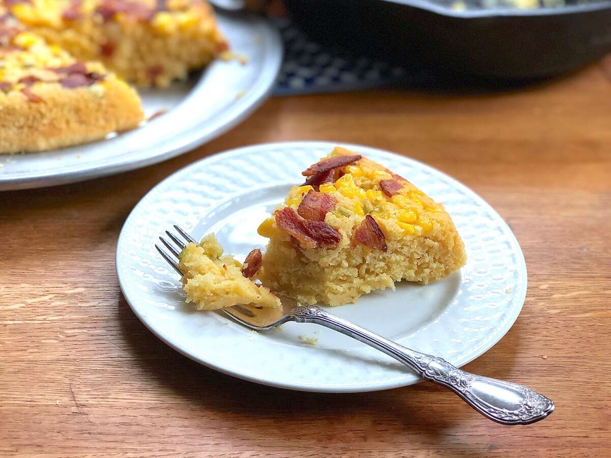 Plated slice of cornbread baked with a topping of scallions, bacon, and corn