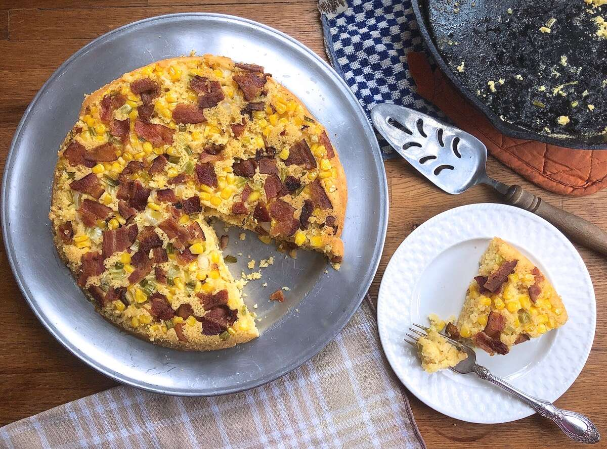 Baked cornbread in a skillet topped with bacon, scallions, and corn; one wedge on a serving plate