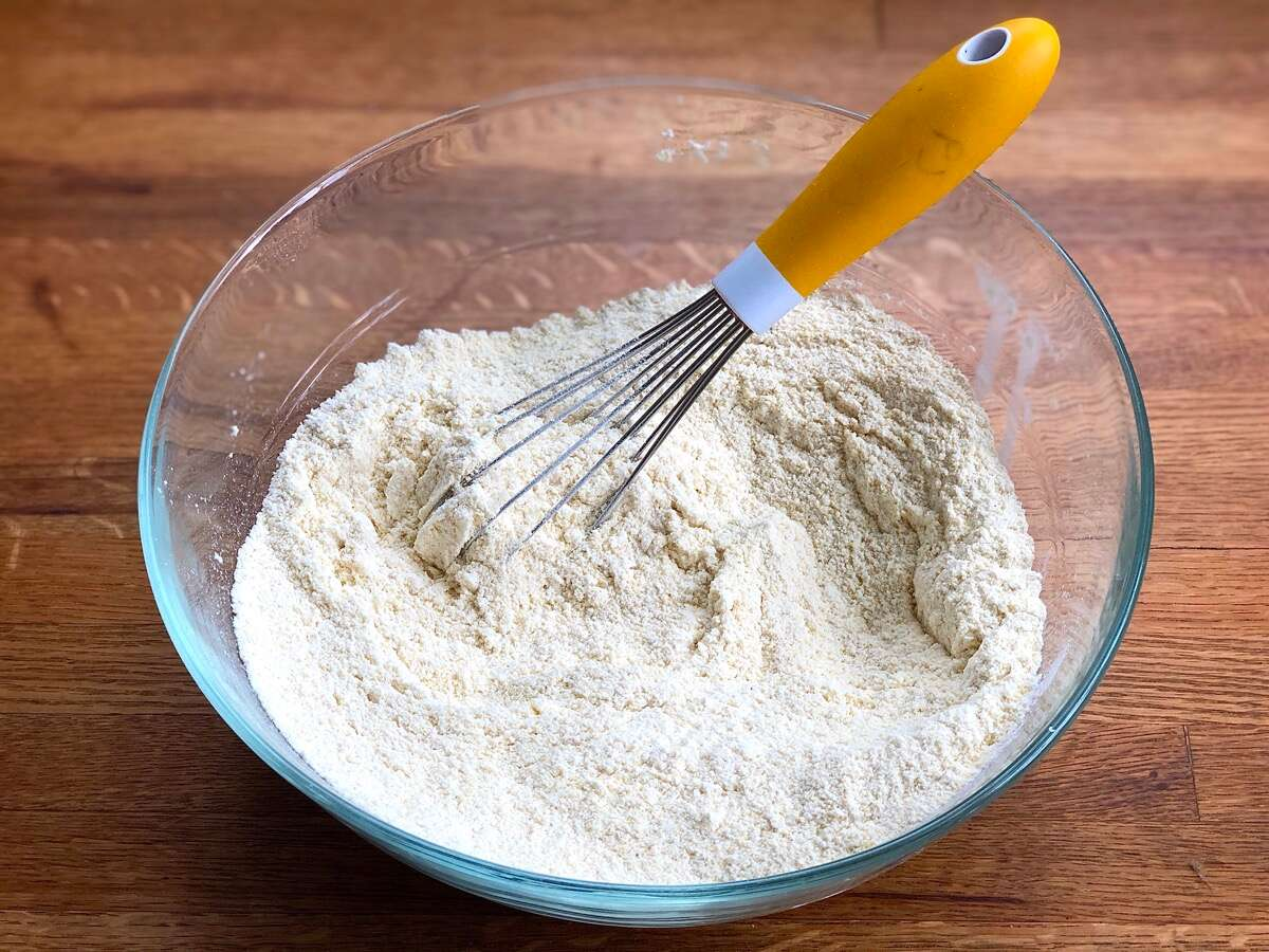 Dry ingredients for cornbread whisked together in a bowl