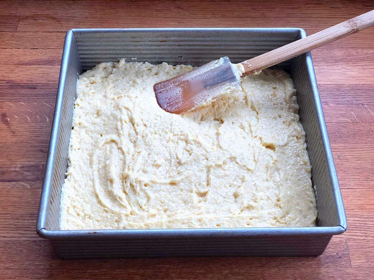"Cornbread batter spread in a 9"" square pan ready to be baked"