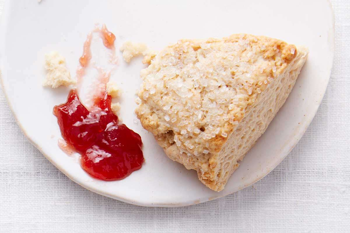 A cream tea scone on a plate next to a schmear of jam