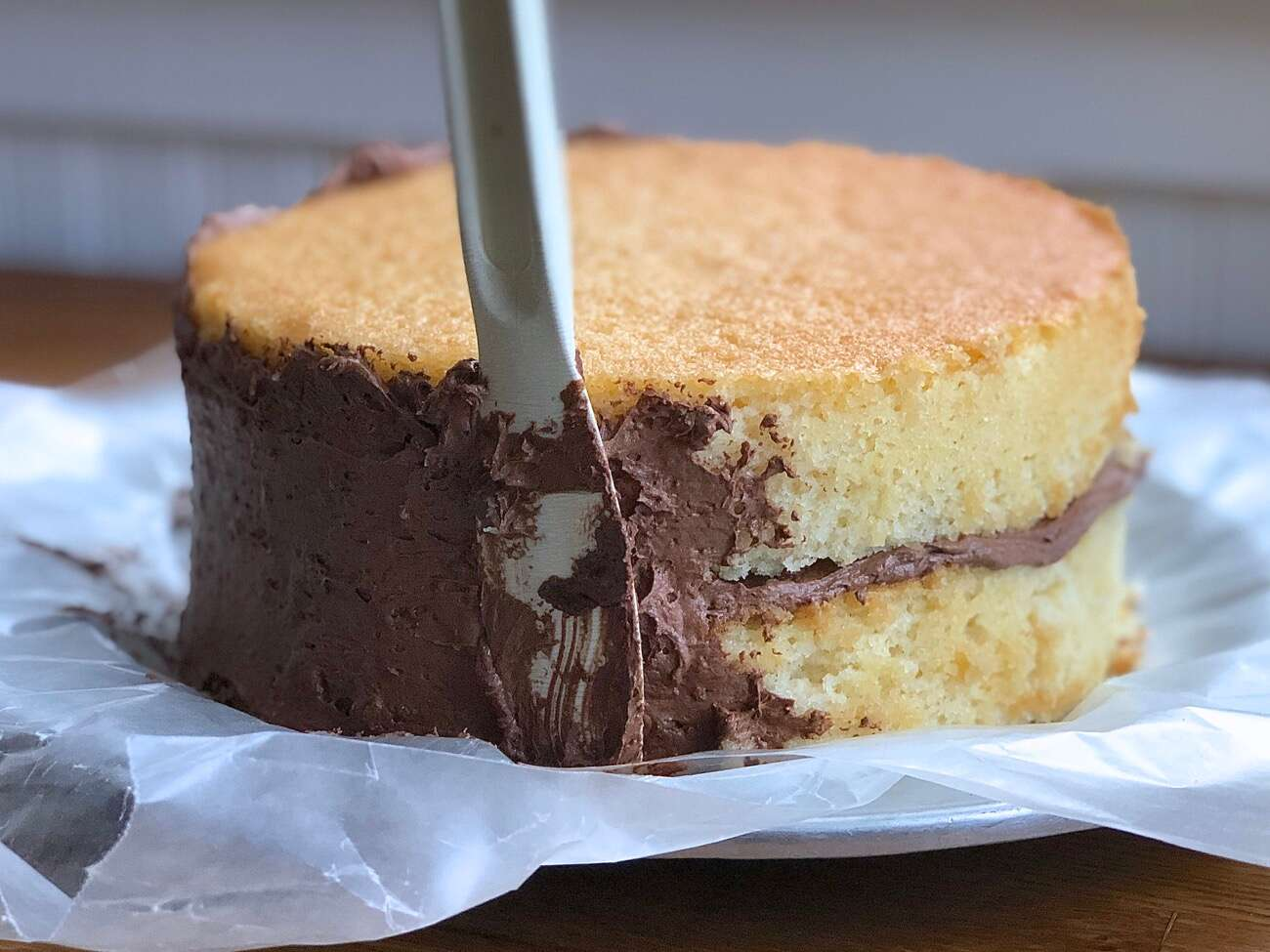 Applying a layer of chocolate frosting — the crumb coat  to a double layer yellow cake.