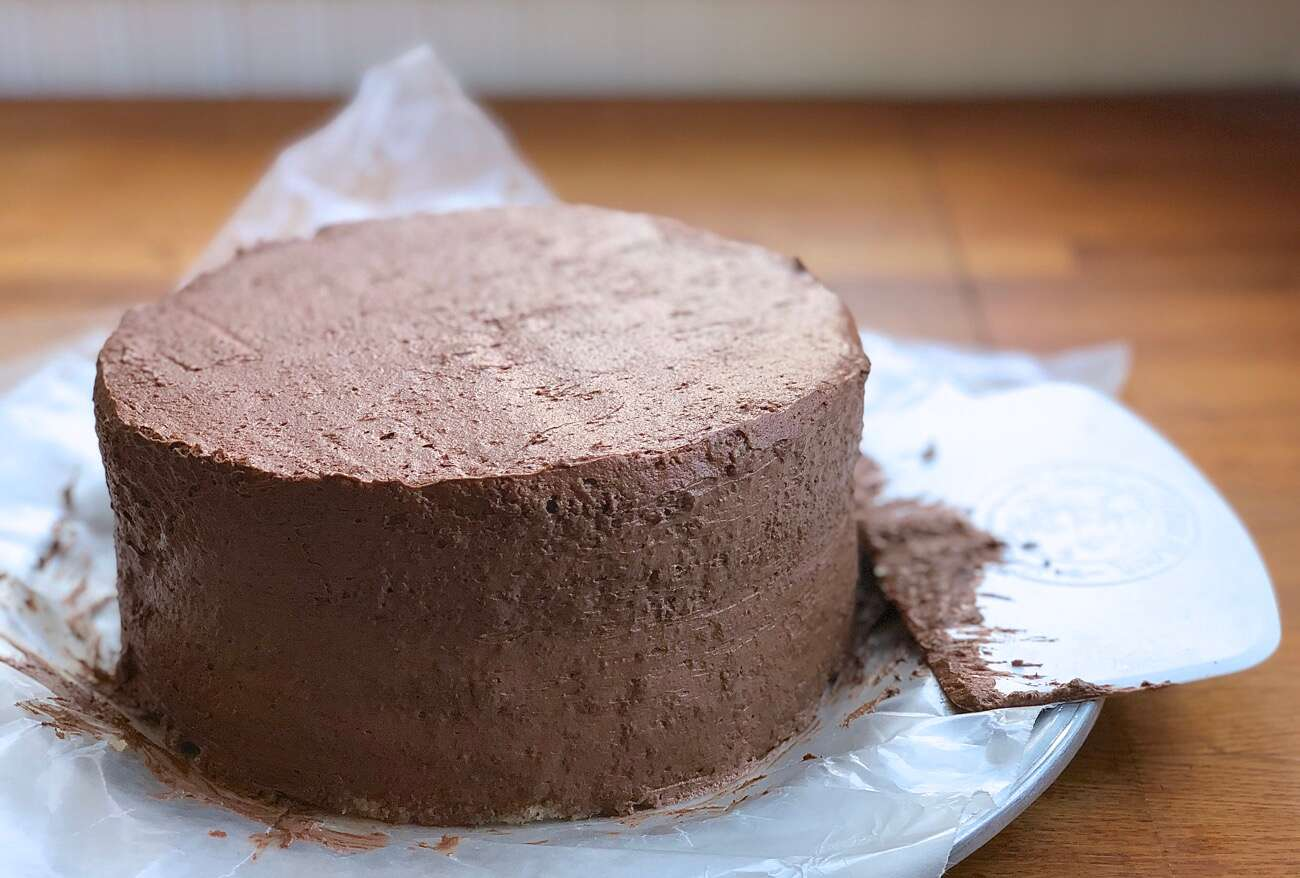 A double-layer yellow cake filled and iced with a thin layer of chocolate frosting known as a crumb coat.