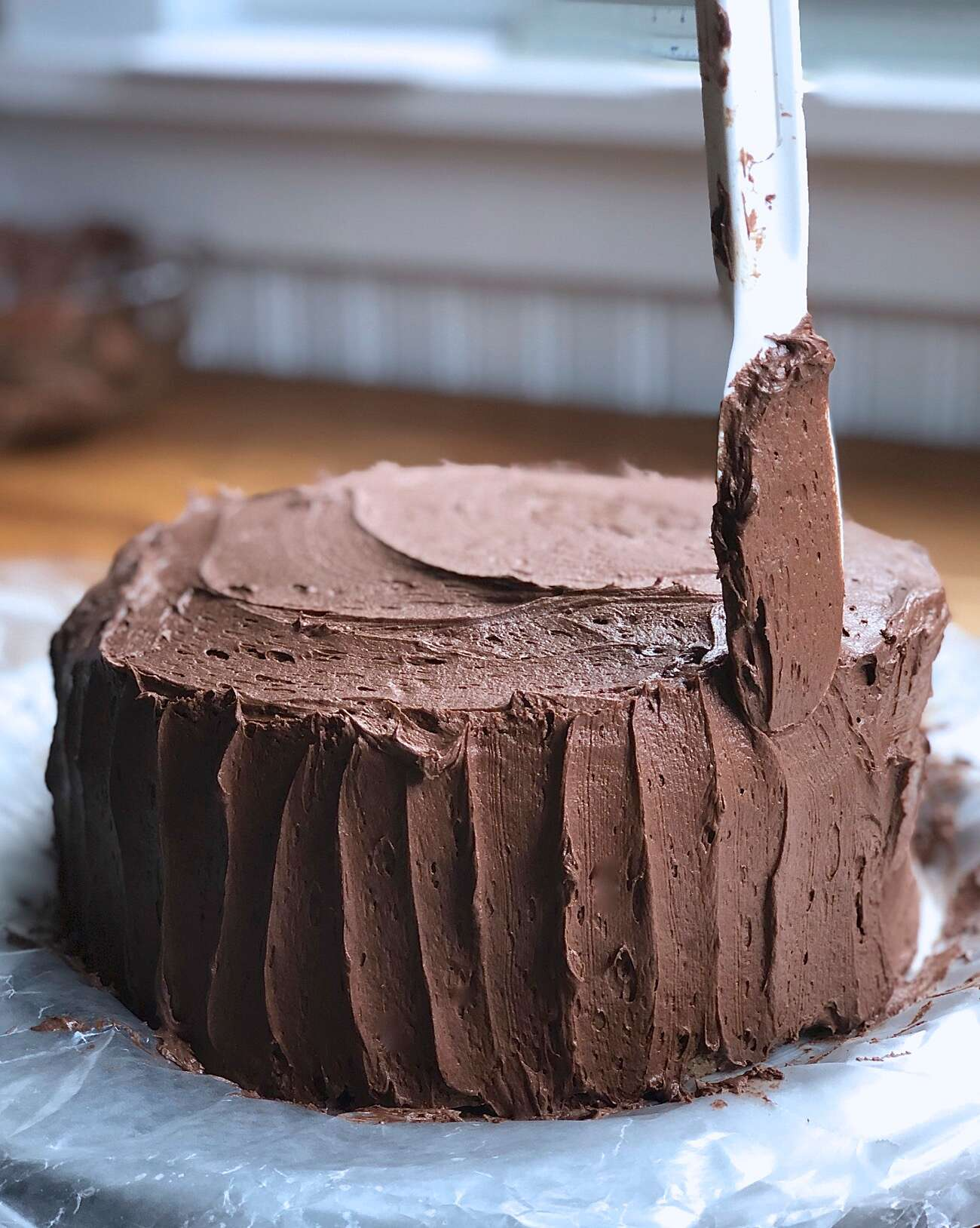 Using a nylon spatula to make vertical scallops in a chocolate-frosted double-layer yellow cake.