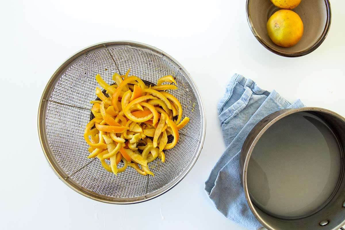 Blanched orange peels in a colander, with a saucepan with sugar and water