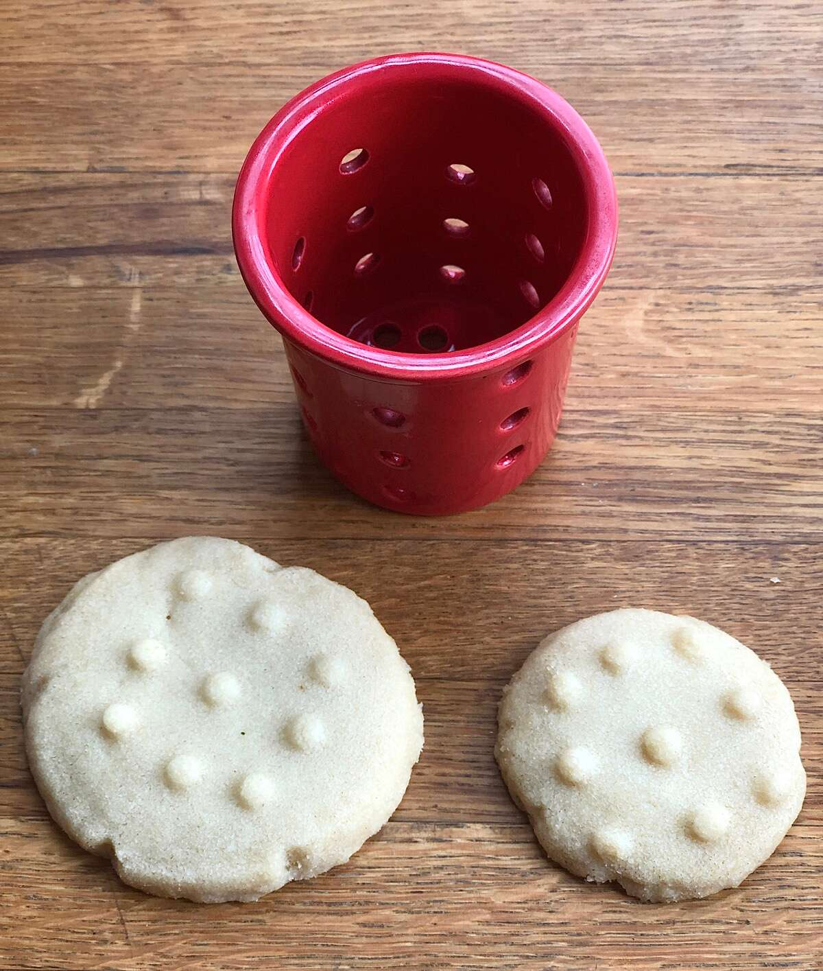 Two chocolate cookies on a table, one large, one small, showing how the imprint made with a tea strainer covers the small cookie, but only partially covers the large one.