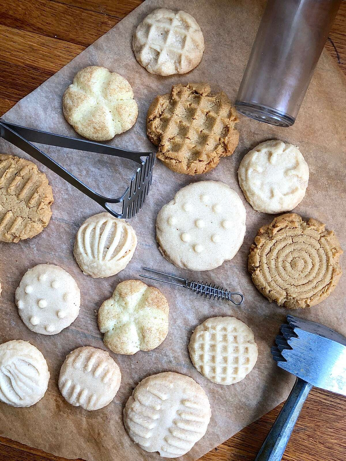An assortment of cookies — peanut butter, shortbread, and Snickerdoodles — with imprinted tops, and the tools used to imprint.