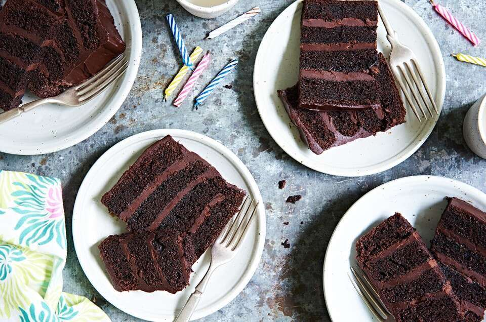 Four-layer fudge cake with chocolate frosting, sliced on a plate.